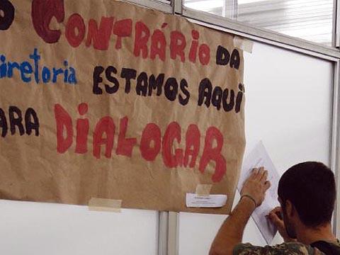 Aluno assina abaixo-assinado pela revogação dos processos durante protesto na porta da sala da Congregação (foto: Francine Segawa)