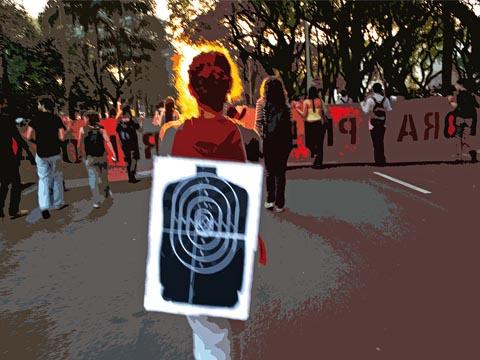 No ato do dia 9 de junho, pouco antes do confronto com a PM, aluna carrega alvo como protesto à presença policial no campus (foto: Guilherme Minotti/arte: Vandson Lima)