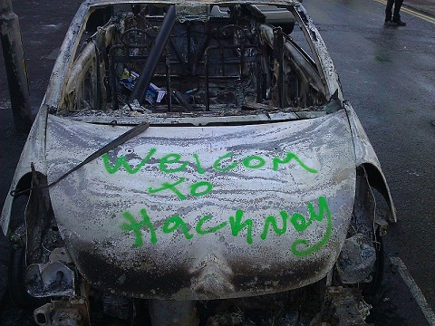 "Carro incendiado e graffitado ""Welcom to Hackney"", bairro londrino (foto: Alastair)"