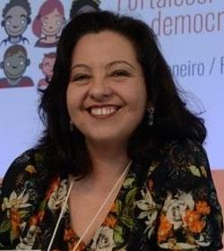 Cristiane Cabral sorri para a foto. Ela está sentada na mesa do Congresso. Ao funo, vemos o painel do Congresso