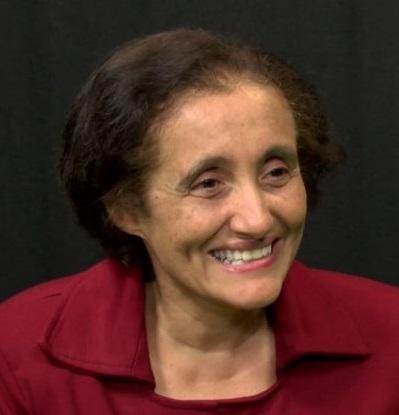 Professora Ester Sabino sorri em perfil. Usa camisa vermelho escuro com gola
