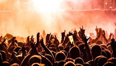 Pessoas em uma plateia estão de costas e com mãos levantadas, enquanto, no palco, uma intensa luz alaranjada é emitida.